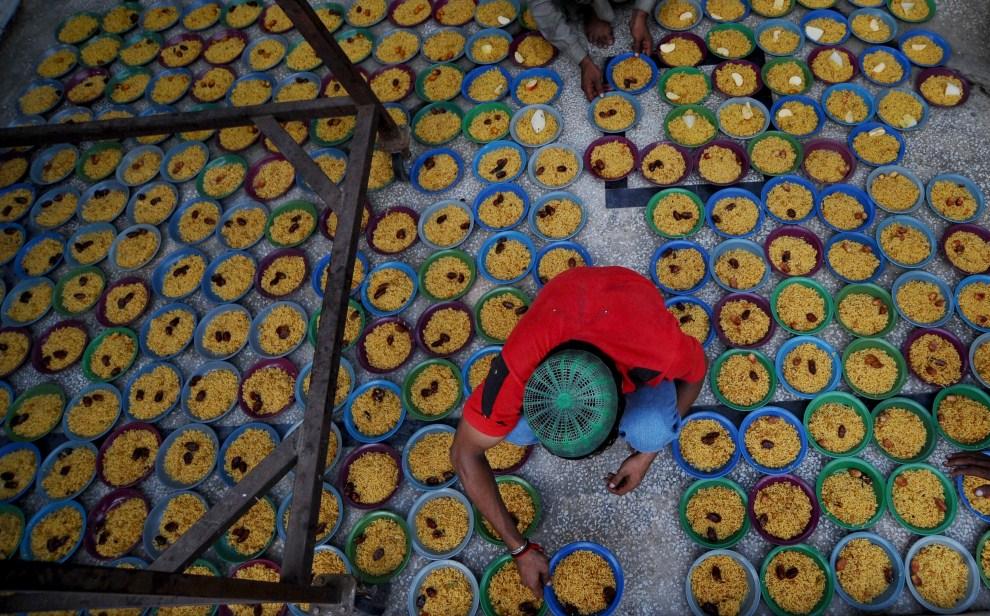 14. PAKISTAN, Lahore, 6 sierpnia 2011: Chłopiec przygotowuje miski z posiłkami. AFP PHOTO/ Arif ALI