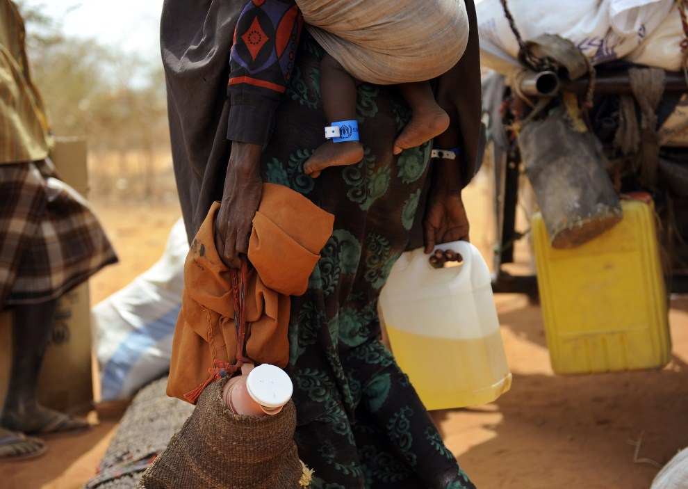 14th KENYA, Dadaab, August 14, 2011: a refugee from Somalia, carrying a child and containers with water. AFP PHOTO / Tony Karumba