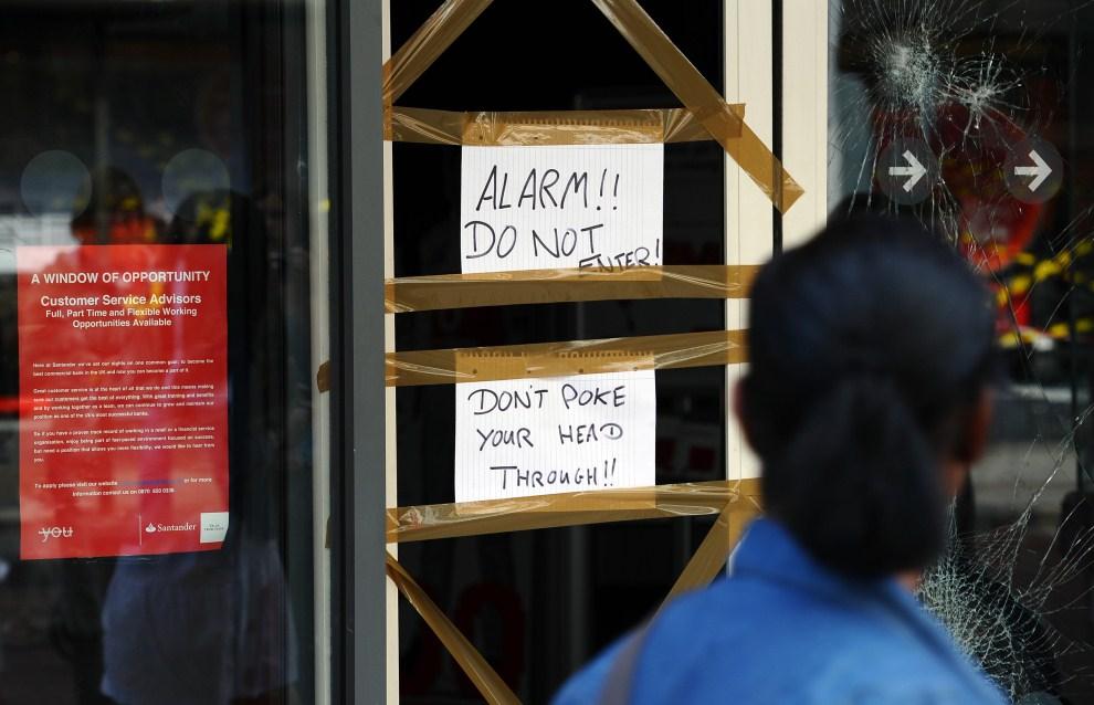 14. WIELKA BRYTANIA, Londyn, 9 sierpnia 2011: Kartki w miejscu rozbitych drzwi informujące o zakazie wchodzenia do budynku banku. AFP PHOTO/PAUL ELLIS