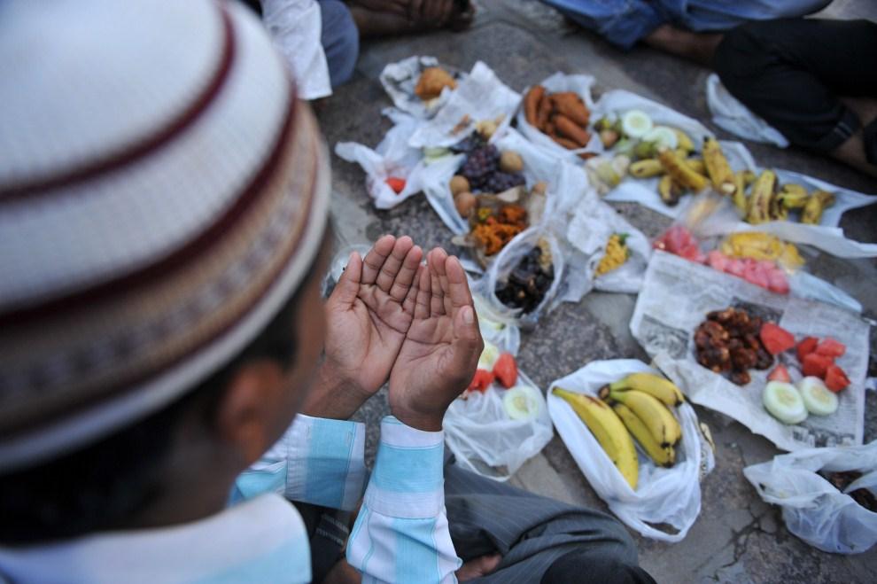 15. INDIE, Hyderabad, 2 sierpnia 2011: Muzułmanin modli się przed posiłkiem. AFP PHOTO/NOAH SEELAM