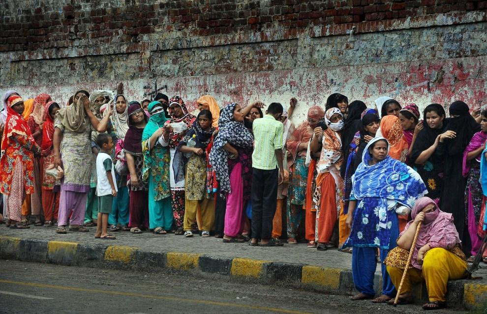 16. PAKISTAN, Lahore, 7 sierpnia 2011: Kobiety w kolejce do punktu gdzie rozdawana jest żywności. AFP PHOTO/Arif ALI