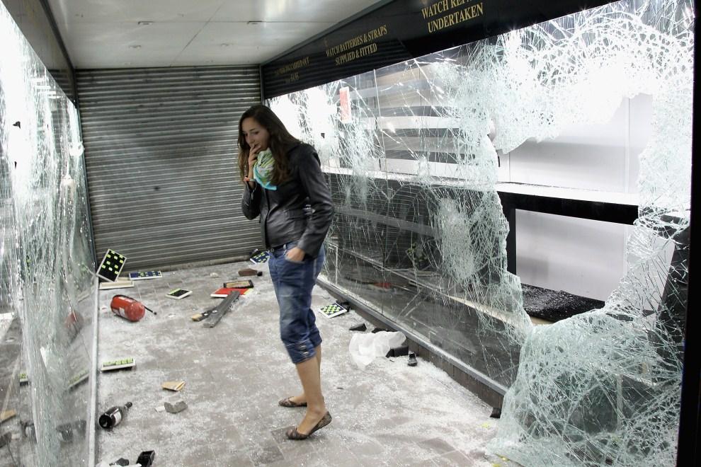 15. WIELKA BRYTANIA, Londyn, 8 sierpnia 2011: Dziewczyna patrzy na okradziony i zdemolowany lombard. (Foto: Chris Jackson/Getty Images)
