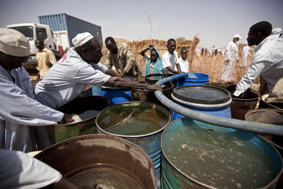 17. SUDAN, Al Srief, 25 lipca 2011: Mężczyzna napełnia beczki wodą zdatną do picia. AFP PHOTO/UNAMID/ Albert Gonzalez Farran