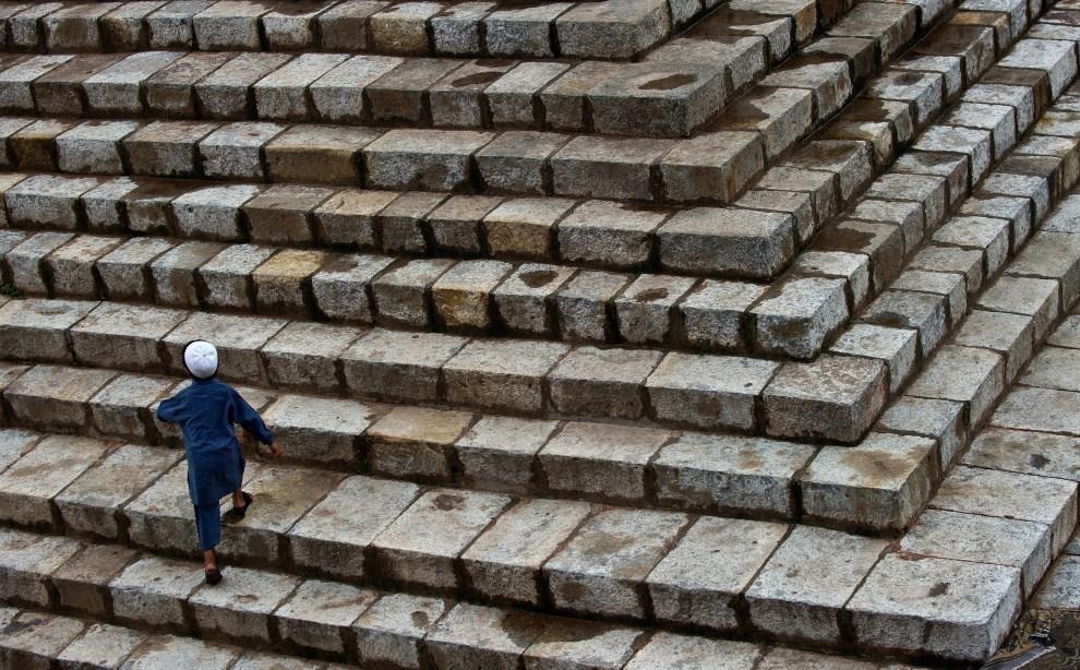 18. INDIE, Nowe Delhi, 5 sierpnia 2011: Chłopiec wchodzi po schodach do wnętrza Feroz Shah Kotla. AFP PHOTO/ MANAN VATSYAYANA