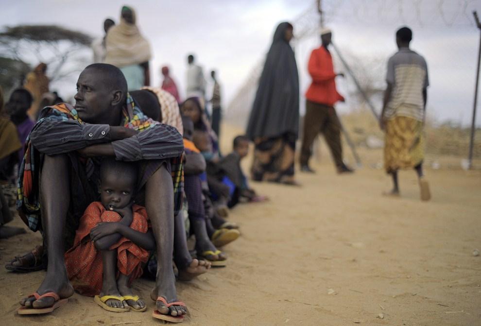 19. KENIA, Dadaab, 2 sierpnia 2011: Somalijczyk z dzieckiem w kolejce do punktu rejestracji w obozie dla uchodźców. AFP PHOTO/Tony KARUMBA