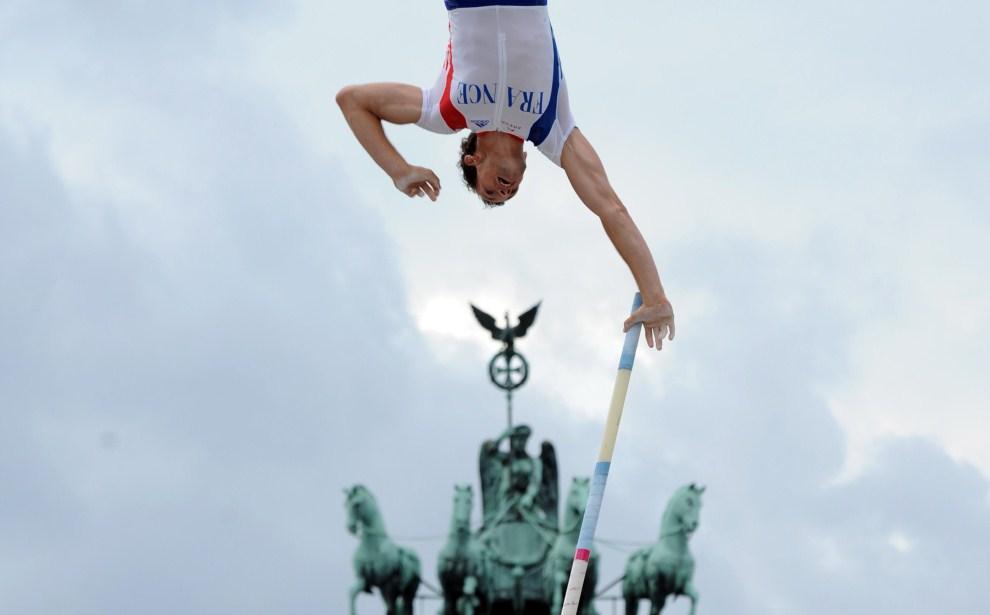 """1. NIEMCY, Berlin, 12 sierpnia 2011: Renaud Lavillenie skacze o tycze w pobliżu Bramy Brandenburskiej w trakcie zawodów """"Berlin fliegt"""".  AFP PHOTO / RAINER JENSEN"""