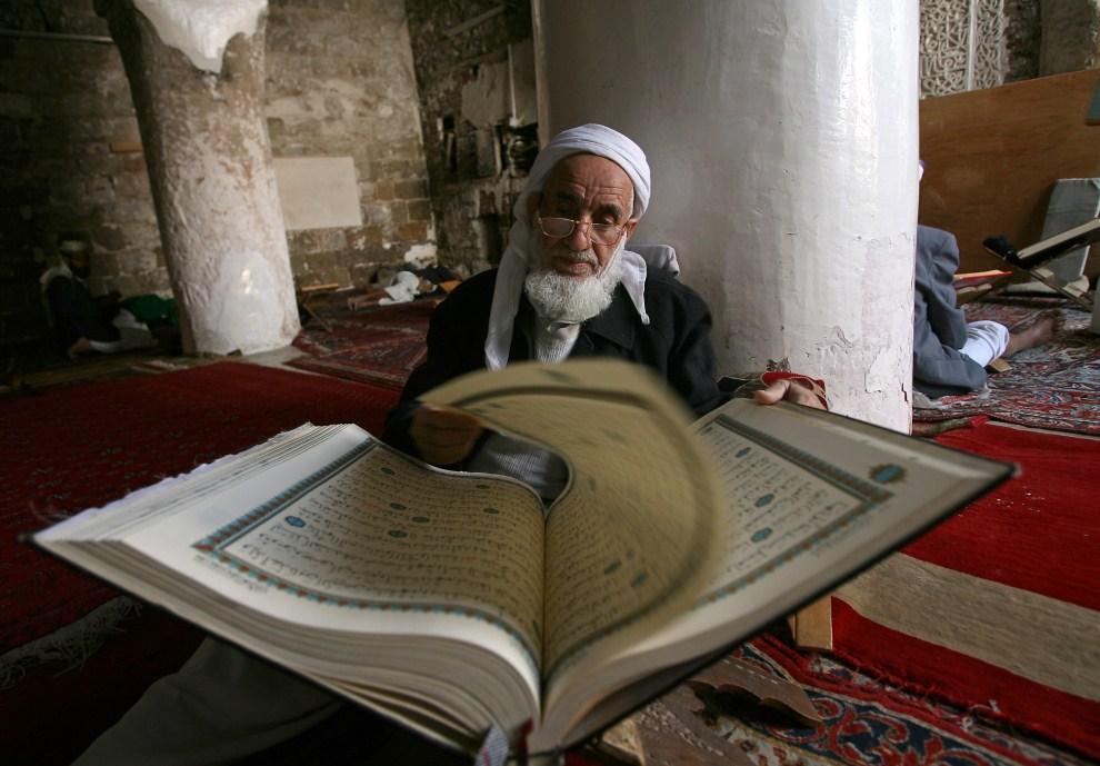 1. JEMEN, Sana, 7 sierpnia 2011: Męzczyzna czytający Koran w meczecie. AFP PHOTO/MOHAMMED HUWAIS
