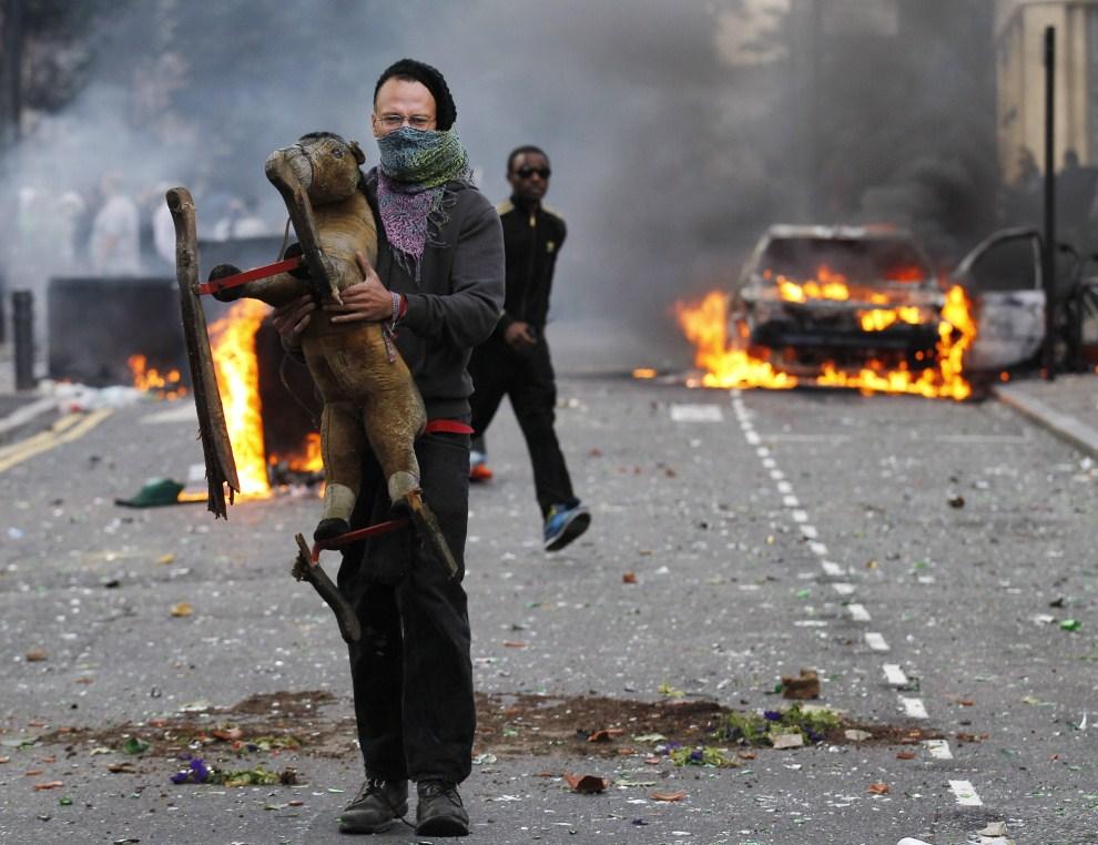 19. WIELKA BRYTANIA, Londyn, 8 sierpnia 2011: Zamaskowany mężczyzna niesie konia na biegunach. EPA/KERIM OKTEN Dostawca: PAP/EPA.