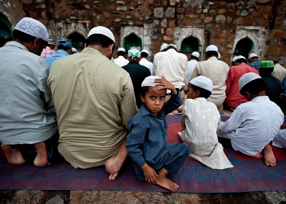 21. INDIE, Nowe Delhi, 5 sierpnia 2011: Chłopiec w otoczeniu modlących się wiernych. AFP PHOTO/ MANAN VATSYAYANA
