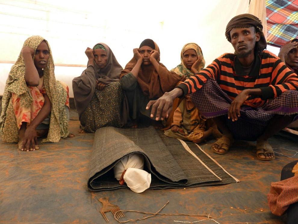 21. ETIOPIA, obóz Kobe, 13 sierpnia 2011: Mohamed Ibrahim (po prawej) przygotowuje do pochówku ciało zmarłego z powodu niedożywienia syna. AFP PHOTO / JENNY VAUGHAN