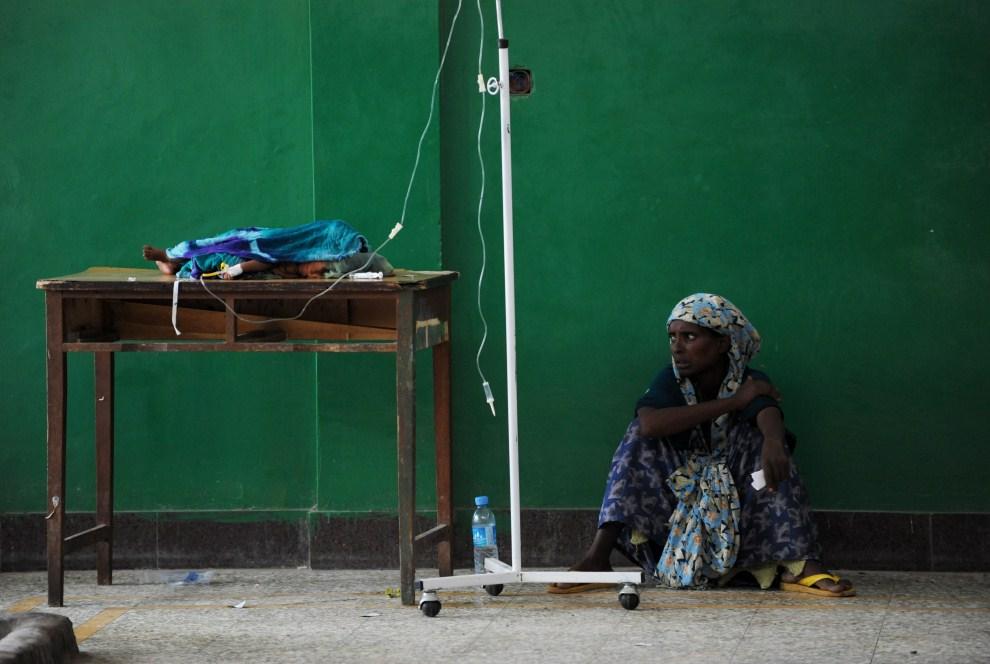 22. SOMALIA, Mogadiszu, 15 sierpnia 2011: Kobieta czeka w pobliżu stołu, na którym leży odżywiane kroplówką dziecko. AFP PHOTO/ROBERTO SCHMIDT