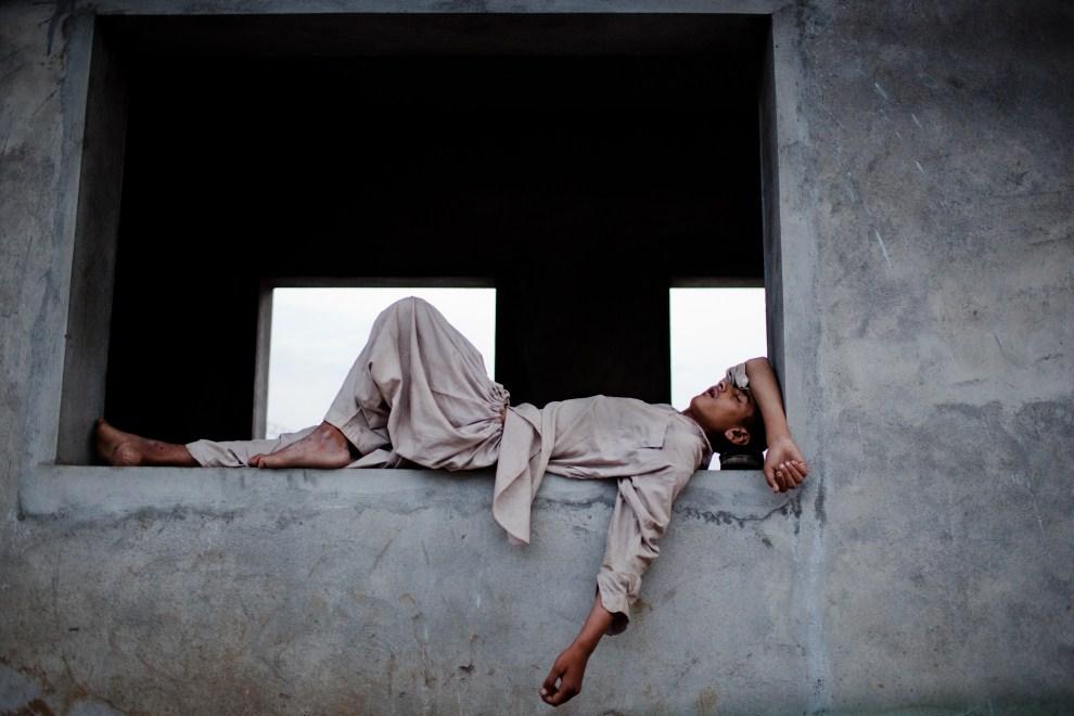 24. PAKISTAN, Rawalpindi, 4 sierpnia 2011: Chłopak śpiący na przystanku autobusowym po zakończeniu iftar. (Foto: Daniel Berehulak/Getty Images)