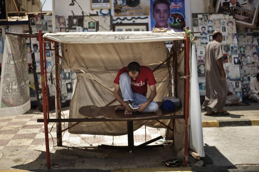 25. LIBIA, Bengazi, 5 sierpnia 2011: Mężczyzna czytający Koran. AFP PHOTO/GIANLUIGI GUERCIA