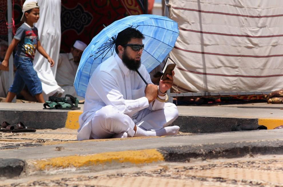 26. LIBIA, Bengazi, 5 sierpnia 2011: Mężczyzna czyta Koran na ulicy w Bengazi. AFP PHOTO/ABDULLAH DOMA