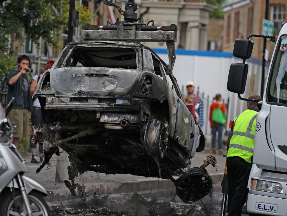 24. WIELKA BRYTANIA, Londyn, 9 sierpnia 2011: Usuwanie z ulicy warku spalonego samochodu. (Foto: Matt Cardy/Getty Images)
