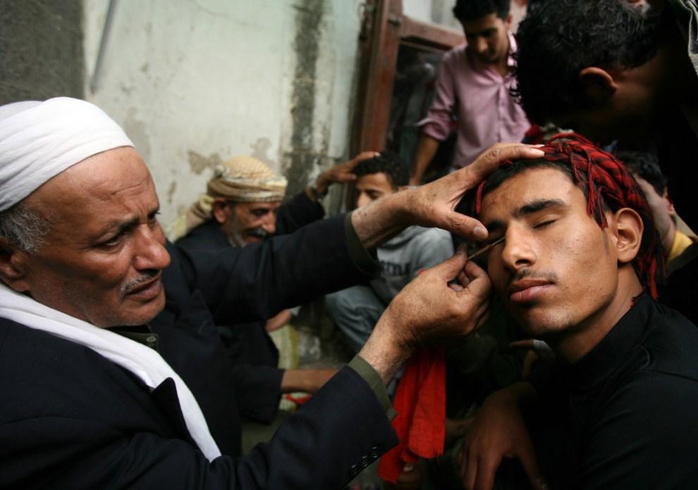 28. JEMEN, Sana, 7 sierpnia 2011: Mężczyzna nakłada makijaż wytworzony z błyszczu ołowiu. AFP PHOTO/MOHAMMED HUWAIS