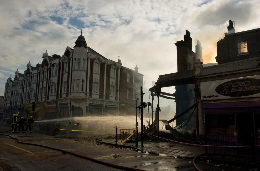 26. WIELKA BRYTANIA, Londyn, 7 sierpnia 2011: Strażacy dogaszają wnętrze podpalonego pubu. AFP PHOTO/LEON NEAL