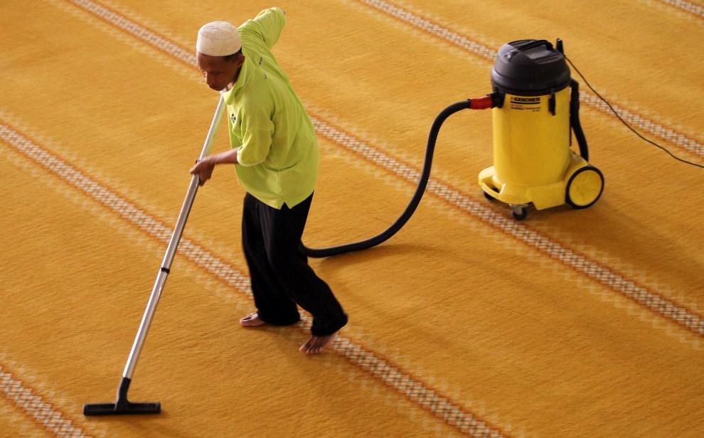 2. MALEZJA, Kuala Lumpur, 31 lipca 2011: Mężczyzna odkurza dywan w jednym z meczetów w Kuala Lumpur. AFP PHOTO / Mohd Rasfan