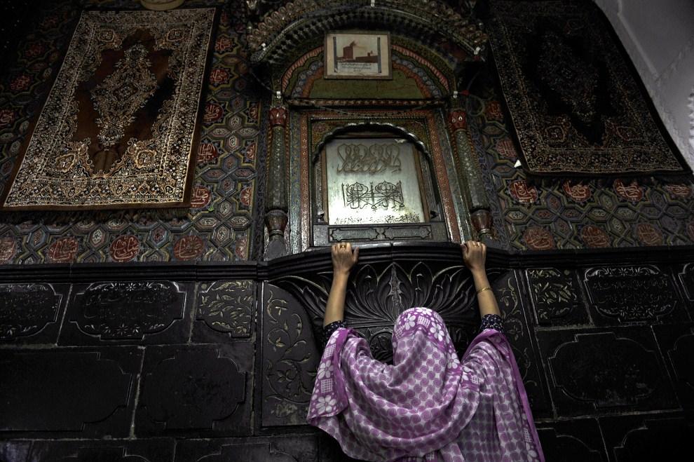 31. INDIE, Śrinagar, 5 sierpnia 2011: Muzułmanka dotyka ściany przed którą modlą się wierni w świątyni Shahi Hamdan. AFP PHOTO / Tauseef MUSTAFA