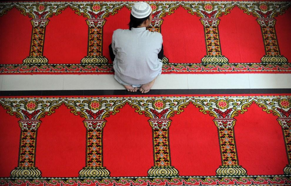 3. INDONEZJA, Dżakarta, 7 sierpnia 2011: Mężczyzna czeka na rozpoczęcie modlitwy w meczecie. AFP PHOTO / ADEK BERRY