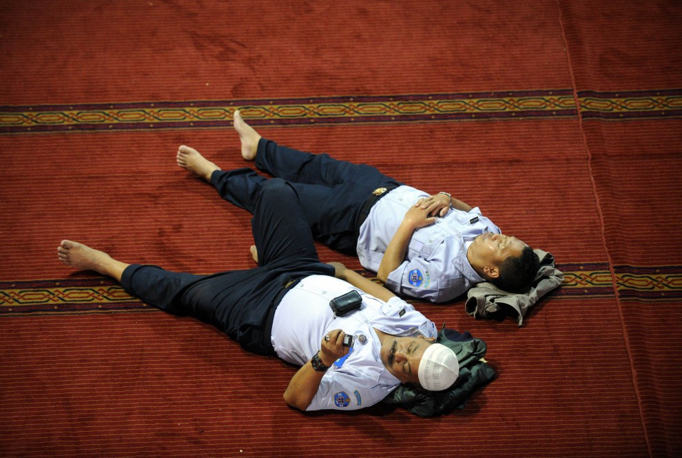 6. INDONEZJA, Dżakarta, 1 sierpnia 2011: Mężczyźni odpoczywają w oczekiwaniu na rozpoczęcie modlitwy. AFP PHOTO / ADEK BERRY