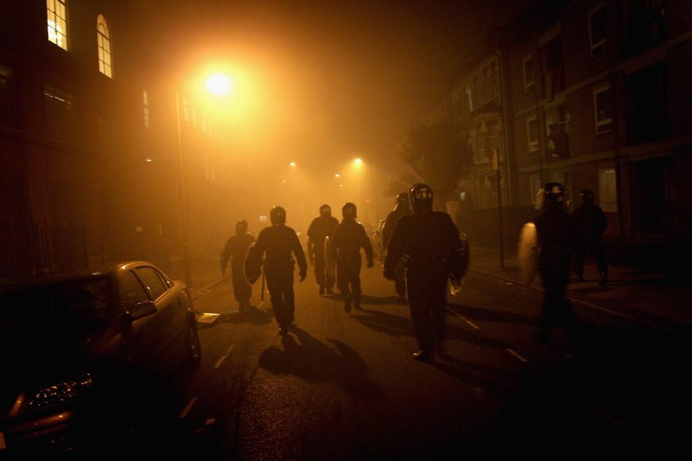 6. WIELKA BRYTANIA, Londyn, 8 sierpnia 2011: Policjanci biegną w kierunku podpalonego budynku przy Clapham Junction. (Foto: Chris Jackson/Getty Images)