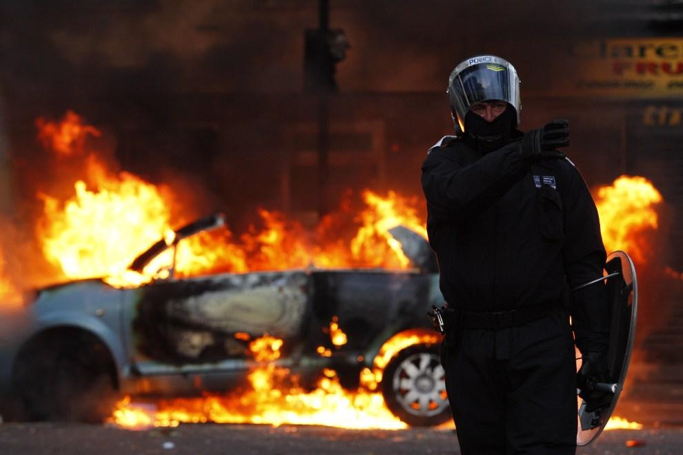 7. WIELKA BRYTANIA, Londyn, 8 sierpnia 2011: Policjant na tle podpalonego samochodu. (Foto: Dan Istitene/Getty Images)