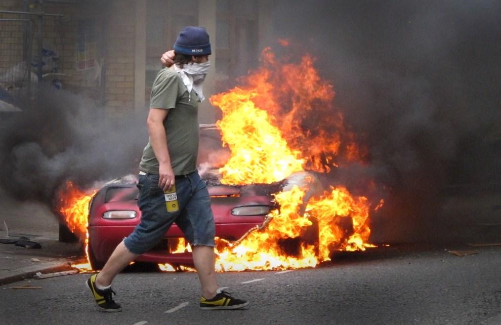 9. WIELKA BRYTANIA, Londyn, 8 sierpnia 2011: Zamaskowany mężczyzna przed sklepem w dzielnicy Hackney. (Foto: Peter Macdiarmid/Getty Images)