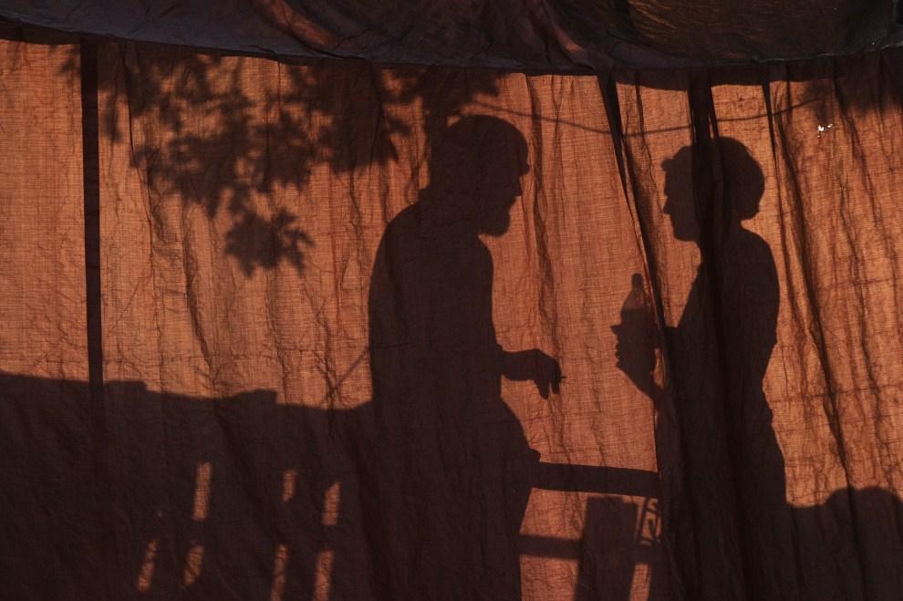 11. WIELKA BRYTANIA, Basildon, 19 września 2011: Sylwetki ludzi prześwitujące przez jeden z namiotów likwidowanego obozowiska koczowników. AFP PHOTO / CARL COURT
