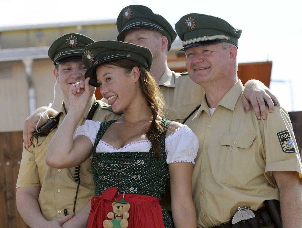 15. NIEMCY, Monachium, 17 września 2011: Dziewczyna pozuje do zdjęcia w towarzystwie policjantów. AFP PHOTO / ANDREAS GEBERT