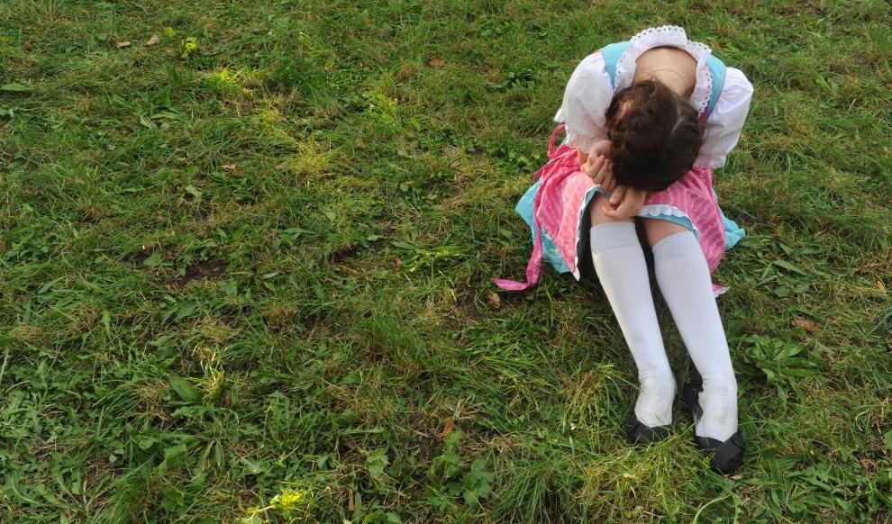 19. NIEMCY, Monachium, 17 września 2011: Dziewczyna ubrana w dirndl odpoczywa na łące w pobliżu Theresienwiese. AFP PHOTO/CHRISTOF STACHE
