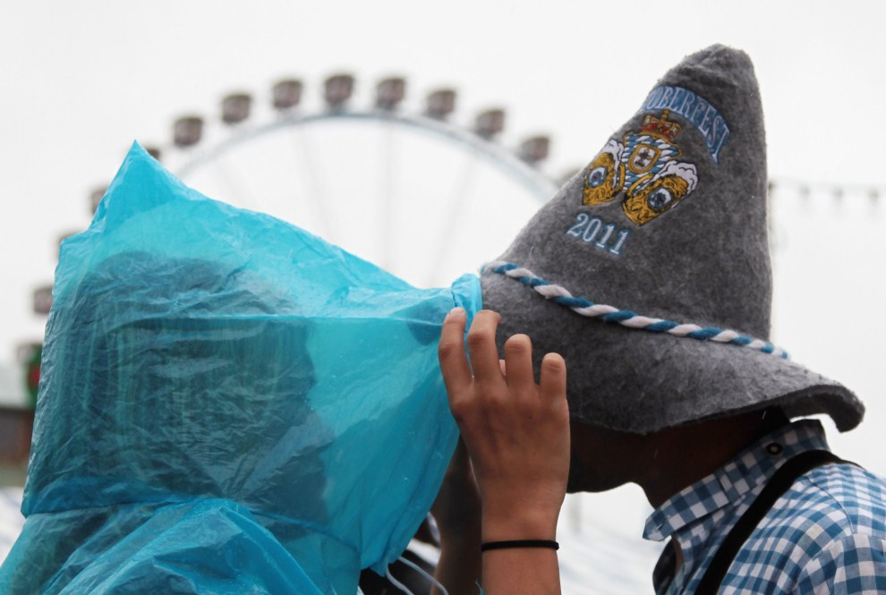23. NIEMCY, Monachium, 18 września 2011: Para uczestników Oktoberfest stara chronić się przed deszczem. (Foto: Johannes Simon/Getty Images)