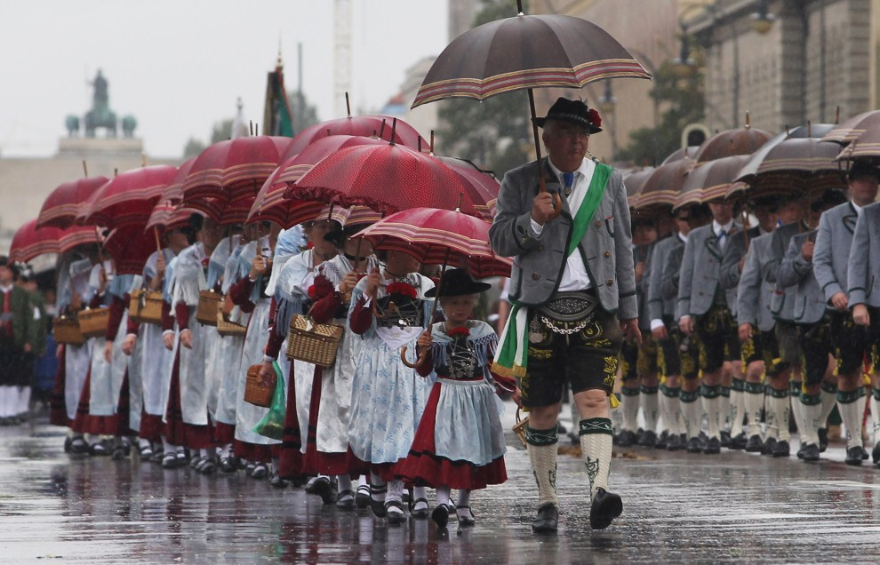 3. NIEMCY, Monachium, 18 września 2011: Uczestnicy parady w drugim dniu Oktoberfest chronią się przed deszczem. (Foto: Alexandra Beier/Getty Images)