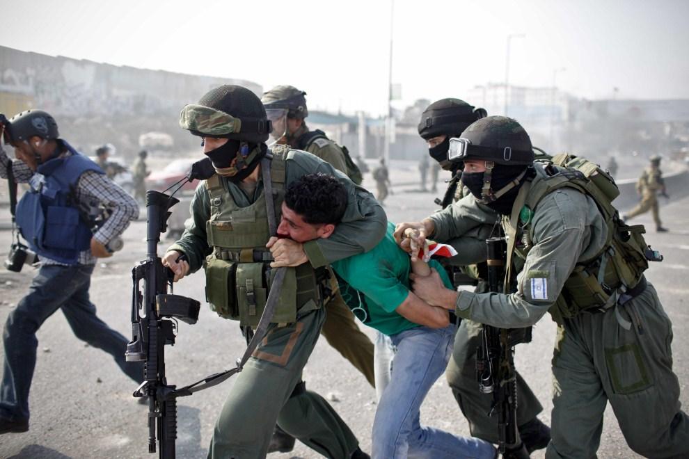 6. ZACHODNI BRZEG, Kalandia, 21 września 2011: Izraelscy funkcjonariusze aresztują młodego Palestyńczyka uczestniczącego w zamieszkach. AFP PHOTO/STR