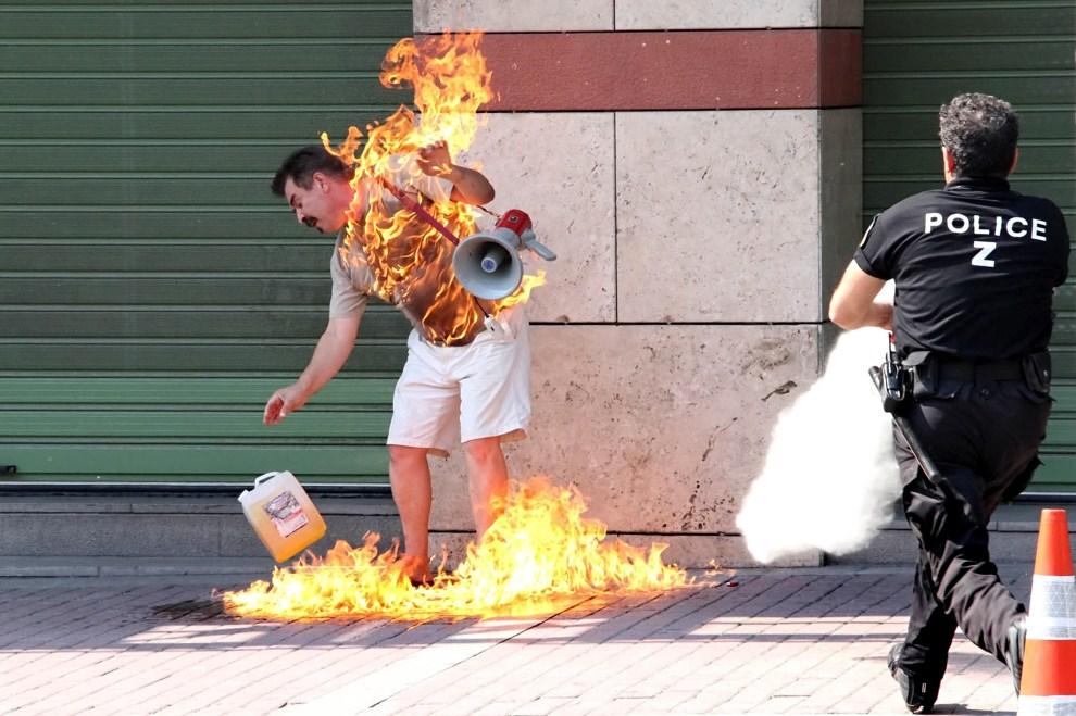 9. GRECJA, Saloniki, 16 września 2011: Policjant stara się ugasić mężczyznę, który podpalił się przed jednym z banków. AFP PHOTO/ NONTAS STYLIANIDIS