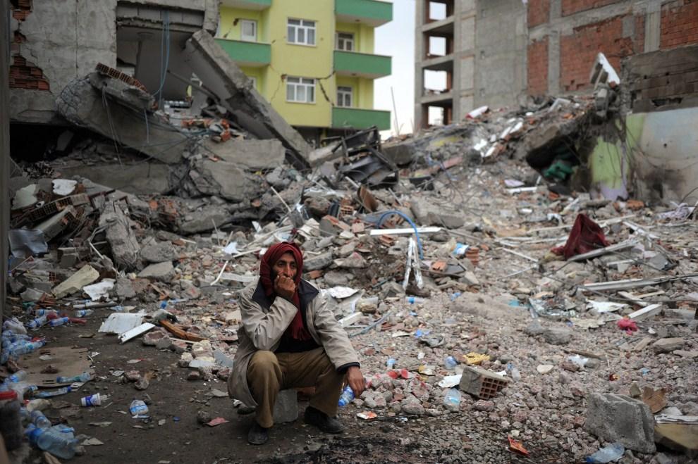 12. TURCJA, Ercis 26 października 2011: Mężczyzna na gruzach budynku zniszczonego przez trzęsienie ziemi. AFP PHOTO / DIMITAR DILKOFF