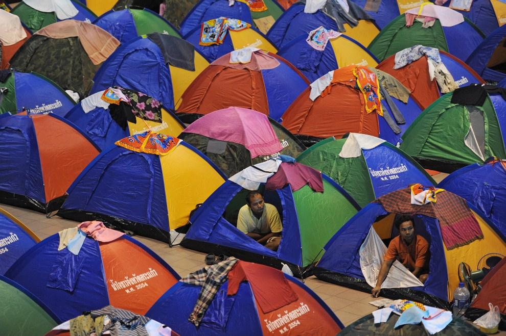 13. TAJLANDIA, Bangkok, 27 października 2011: Mieszkańcy miasteczka namiotowego zorganizowanego dla ofiar powodzi. AFP PHOTO/Christophe ARCHAMBAULT