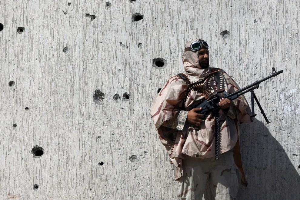 14. LIBIA, Syrta, 10 października 2011: Bojownik NTC na tle ostrzelanego muru. (Foto: Majid Saeedi/Getty Images)