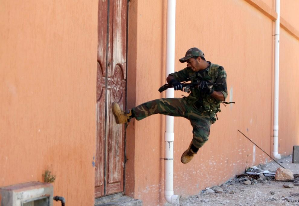 20. LIBIA, Syrta, 12 października 2011: Bojownik NTC stara się wyważyć drzwi jednego z budynków przy opanowanej ulicy. AFP PHOTO/AHMED AL-RUBAYE