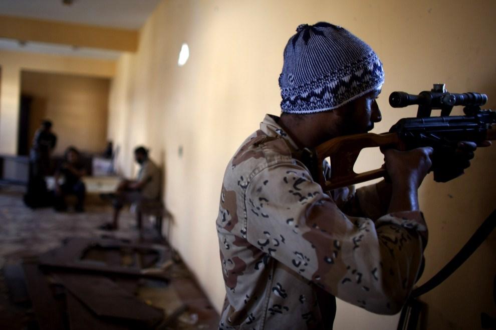 21. LIBIA, Syrta, 14 października 2011: Snajper NTC obserwuje teren w pobliżu zajętego budynku. (Foto: Majid Saeedi/Getty Images)