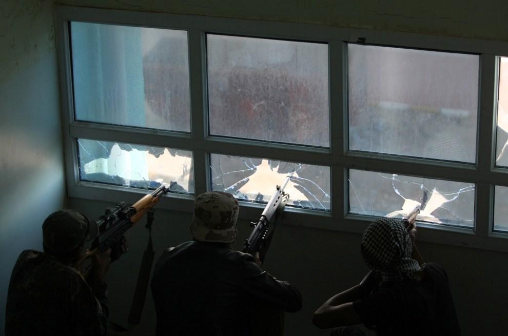 22. LIBIA, Syrta, 14 października 2011: Rebelianci ostrzeliwują pozycje oddziałów wiernych Kadafiemu. AFP PHOTO/AHMAD AL-RUBAYE