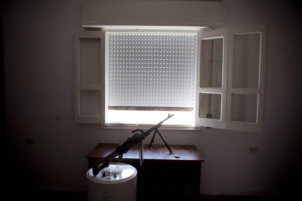 23. LIBIA, Syrta, 8 października 2011: Stanowisko karabinu maszynowego w oknie, zajętego przez rebeliantów, budynku. (Foto: Majid Saeedi/Getty Images)