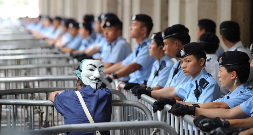 28.CHINY, Hong Kong, 25 czerwca 2010: Zwolennik przemian demokratycznych i kordon policji podczas demonstracji w centrum miasta. AFP PHOTO/MIKE CLARKE