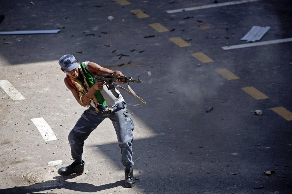 26. LIBIA, Syrta, 8 października 2011: Rebeliant podczas wymiany ognia na ulicy w Syrcie. (Foto: Majid Saeedi/Getty Images)