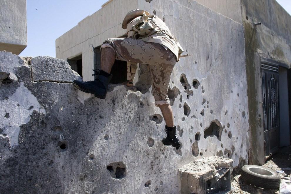 29. LIBIA, Syrta, 12 października 2011: Bojownik NTC chroni się za murem podczas walk w centrum Syrty. (Foto: Majid Saeedi/Getty Images)