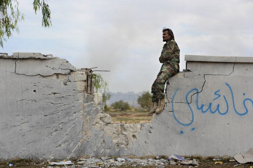 30. LIBIA, Syrta, 19 października 2011: Rebeliant siedzi na wyrwie w ostrzelanym murze. AFP PHOTO/PHILIPPE DESMAZES
