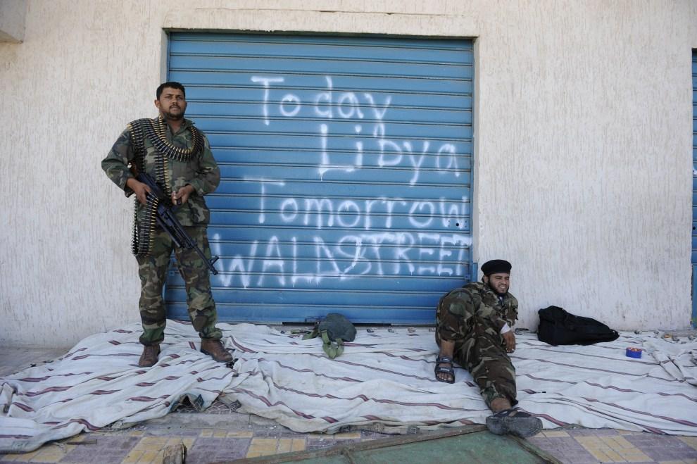 31. LIBIA, Syrta, 16 października 2011: Bojownicy NTC odpoczywają przed wejściem do sklepu w centrum Syrty. Napis na rolecie głosi: Dziś Libia Jutro Wallstreet. AFP PHOTO/PHILIPPE DESMAZES
