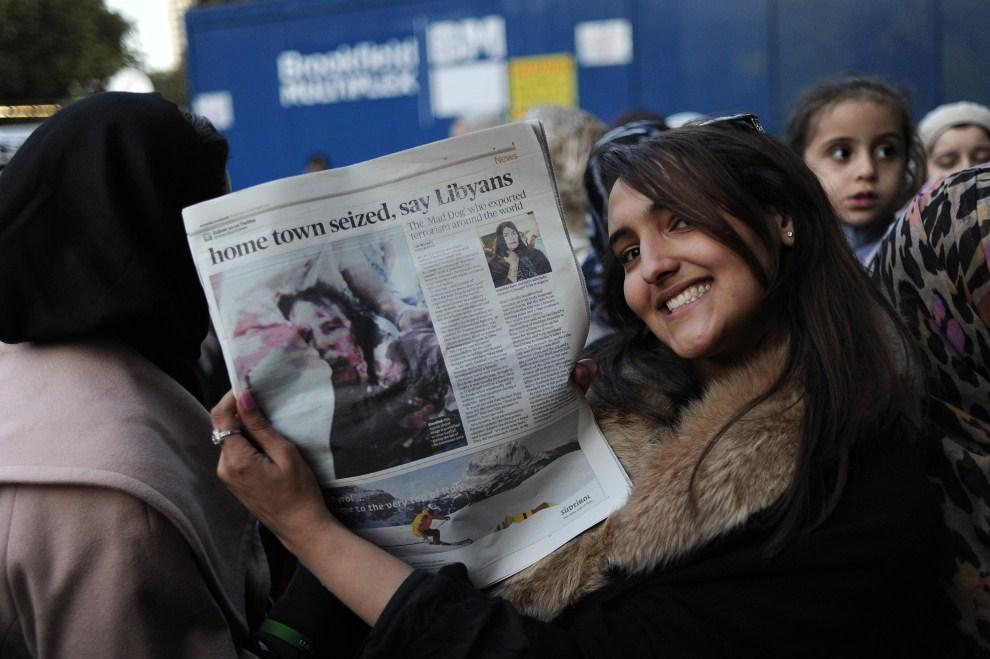32. WIELKA BRYTANIA, Londyn, 20 października 2011: Kobieta trzyma egzemplarz gazety z informacją o śmierci Muammara Kadafiego. AFP PHOTO / CARL COURT