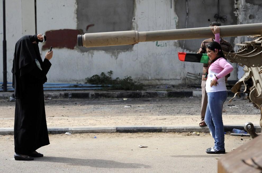 3. LIBIA, Misrata, 23 października 2011: Kobieta fotografuje córkę na tle czołgu. AFP PHOTO/PHILIPPE DESMAZES