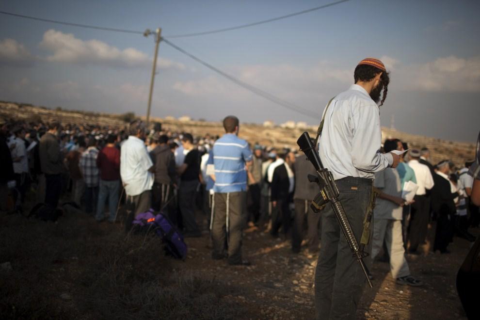 5. ZACHODNI BRZEG, Giv'at Asaf, 27 października 2011: Żydowscy osadnicy podczas wspólnej modlitwy. AFP PHOTO/MENAHEM KAHANA